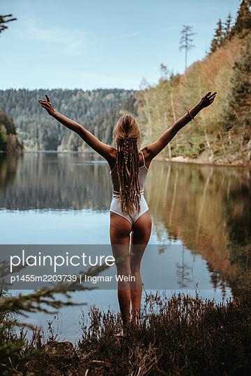 Frau posiert vor ruhigem Bergsee - p1455m2203739 von Ingmar Wein