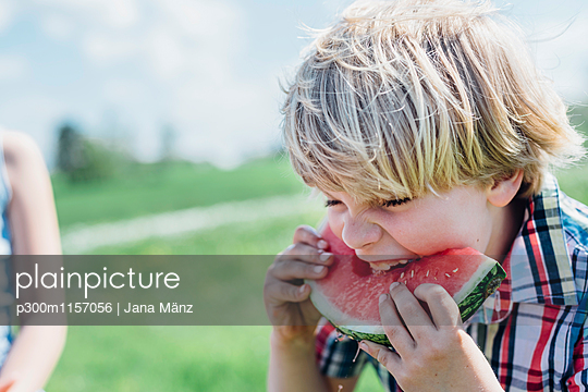Boy outdoors eating slice of watermelon - p300m1157056 by Jana Mänz