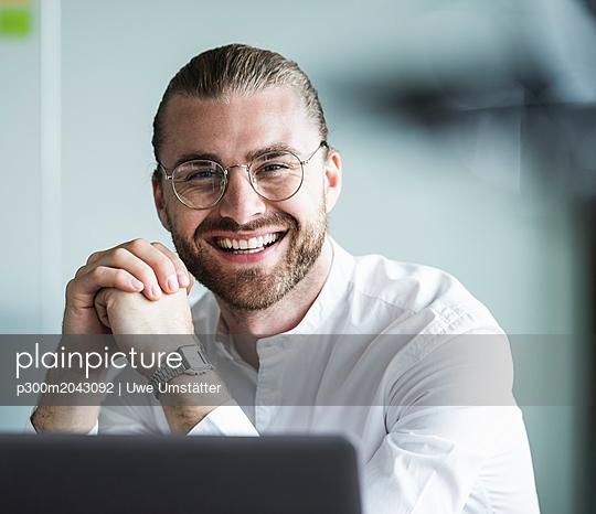 Portrait of smiling young businessman in office - p300m2043092 von Uwe Umstätter