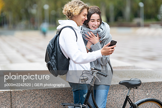 Young friends with bicycle laughing while watching video through smart phone on footpath - p300m2242520 by GER photography