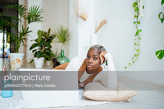 Female entrepreneur with head in hand lying on floor in front of laptop at home - p300m2277410 by Rafa Cortés