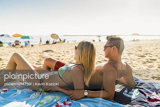Young couple sunbathing on Newport Beach, California, USA - p924m1094756f by Kevin Kozicki