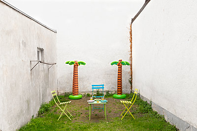Plastic palms and bright garden furniture in a backyard - p1625m2245014 by Dr. med.