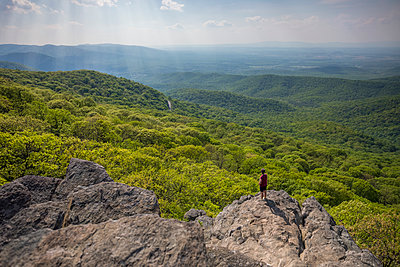 Hiker standing at edge of Humpback Rock, Virginia, USA - p343m2025858 by Ben Girardi
