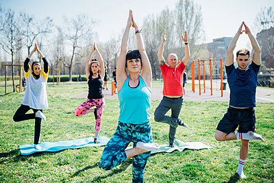 Calisthenics class at outdoor gym, women and men practicing yoga tree pose - p429m2098438 by Eugenio Marongiu