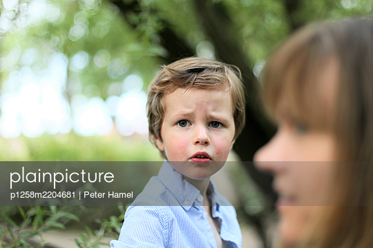 Grumpy boy looking at camera, mother in foreground - p1258m2204681 by Peter Hamel