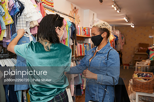 Lesbian women shopping clothes at store during COVID-19 - p300m2290720 by Pete Muller