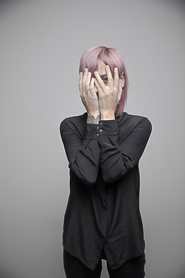 Portrait beautiful non-binary gender person with pink hair hiding behind hands - p1192m2066236 by Hero Images