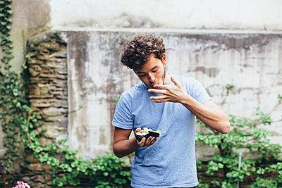 Young man devouring fruit - p586m1044929 by Kniel Synnatzschke