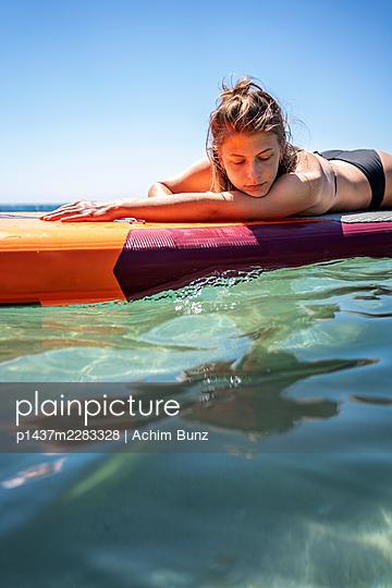 Junge Frau im Bikini auf einem Surfbrett - p1437m2283328 von Achim Bunz