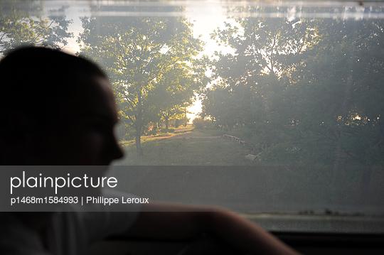 Jugendlicher am Fenster in seinem Wohnwagen  - p1468m1584993 von Philippe Leroux