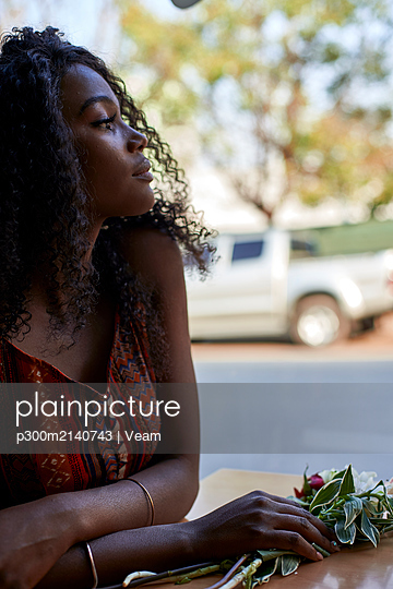 Portrait of young African woman with flowers on the table in a cafe, looking out of window - p300m2140743 by Veam