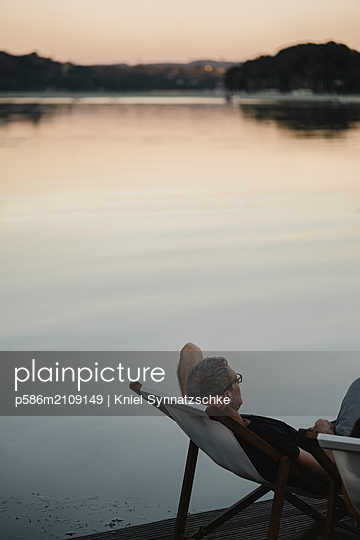 Mature man relaxing in canvas chair at Lake Baldeneysee - p586m2109149 by Kniel Synnatzschke