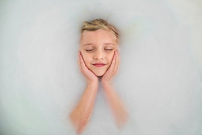 Overhead view of girl with closed eyes resting in bathtub - p1166m1204303 by Cavan Images