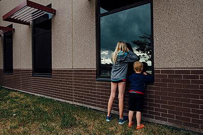 Rear view of siblings peeking through window while standing at backyard - p1166m1524810 by Cavan Images