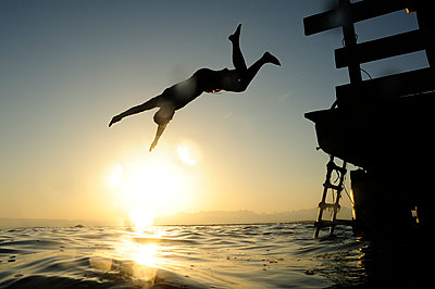 Man jumping fom jetty into the sea at sunset - p300m1505442 by Eyecatcher.pro