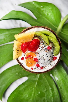 Coconut bowl with variuos fruits, natural yoghurt and seeds on leaf - p300m1587984 von Retales Botijero