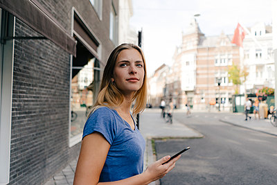 Netherlands, Maastricht, smiling young woman with cell phone in the city looking around - p300m2058874 von Gustafsson