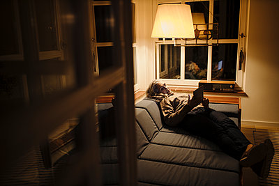 Mature woman using tablet on couch at home in the dark - p300m2155257 by Gustafsson