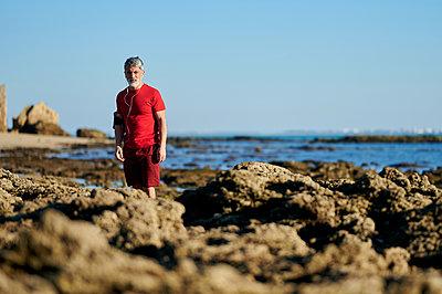 Man standing on rocks at beach - p300m2275690 by Kiko Jimenez