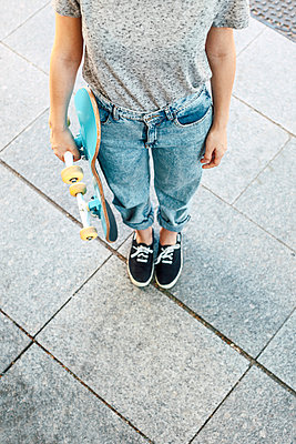 Young female skate boarder with her skateboard, partial view - p300m949771f by Bonninstudio