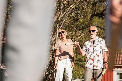 Senior couple in garden playing kubb - p312m2208258 by Plattform