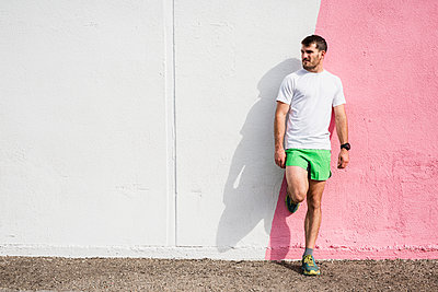 Young male runner leaning against pink and white wall - p924m2074793 by JFCreatives