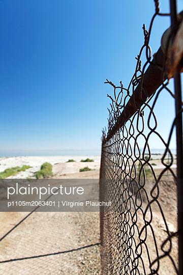 Wire fence on the beach - p1105m2063401 by Virginie Plauchut