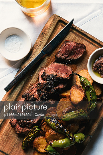 Medium rare cuts of steak and potatoes at a dinner out - p1166m2191924 by Cavan Images
