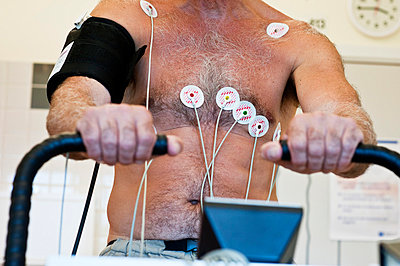 Midsection of a man with electrodes on his body while exercising diagnosis EKG electrocardiograph en - p1025m788559f by Magnus Westerborn