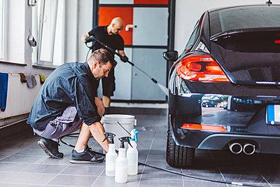 Workers cleaning car in workshop - p1166m2060362 by Cavan Images