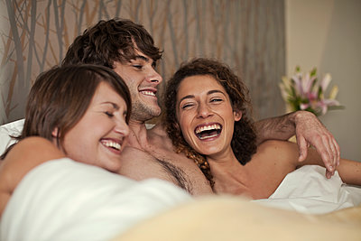 Young man and two women (21-25) in bed together, Cape Town, South Africa - p300m2264566 von LOUIS CHRISTIAN