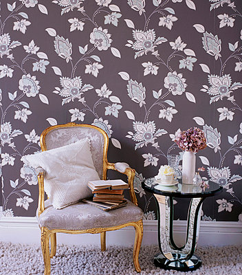 Bold patterned wallpaper in a living room with upholstered chair and mirrored side table - p349m695240 by Emma Lee
