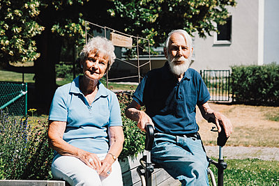Portrait of smiling retired senior man and woman sitting at back yard - p426m2074252 by Maskot