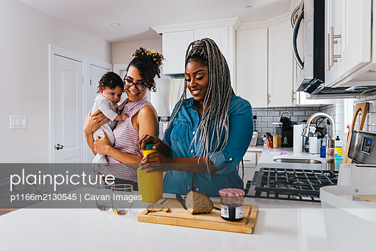 Happy mother carrying baby boy while girlfriend preparing breakfast in kitchen - p1166m2130545 by Cavan Images