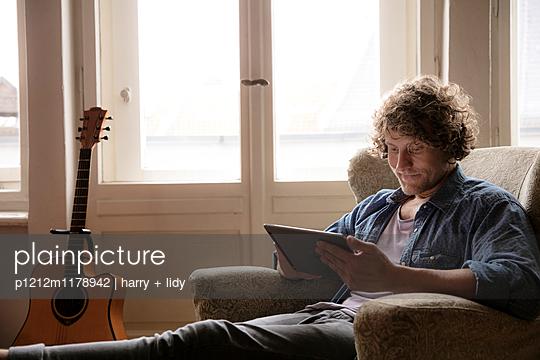 Mann mit Tablet im Sessel - p1212m1178942 von harry + lidy