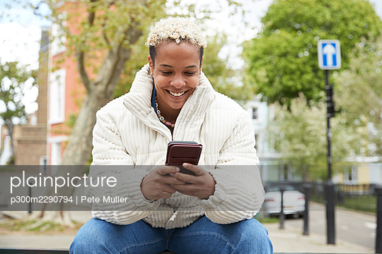 Happy mid adult woman wearing white jacket using smart phone sitting at park - p300m2290794 by Pete Muller