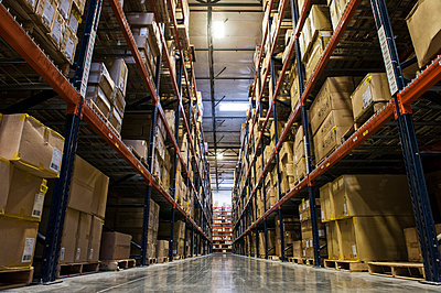 View down an aisle of racks holding cardboard boxes of product on pallets  in a large distribution warehouse - p1100m1575483 by Mint Images