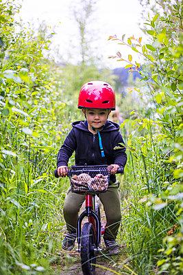 Toddler boy riding balance bike through forest. - p1166m2147354 by Cavan Images