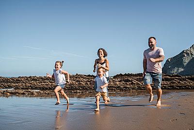 Cheerful family running at beach against sky - p300m2256610 by SERGIO NIEVAS