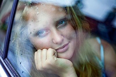 Girl (11-15) daydreaming at car window, Southwold, Suffolk, United Kingdom - p300m2298748 von LOUIS CHRISTIAN
