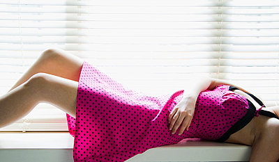 Girl with a pink dress lying down - p4262993f by Tuomas Marttila