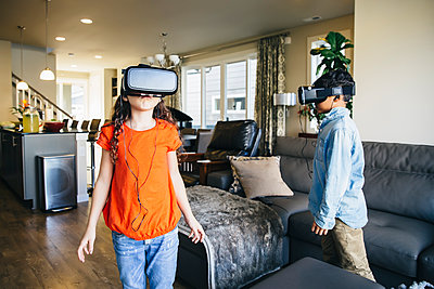 Mixed race children using virtual reality goggles in living room - p555m1305901 by Inti St Clair photography