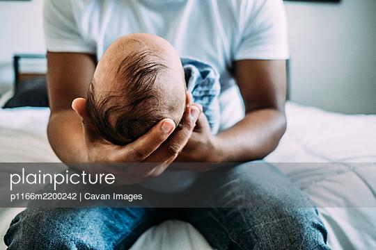 center portrait of dad holding newborn baby - p1166m2200242 by Cavan Images
