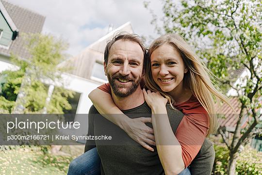 Happy couple standing in their garden - p300m2166721 von Kniel Synnatzschke