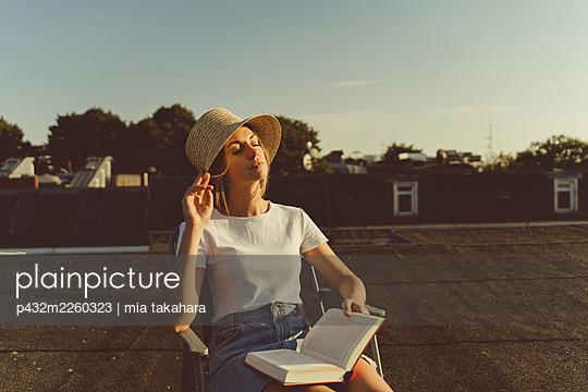 Junge Frau mit Buch auf Hausdach - p432m2260323 von mia takahara