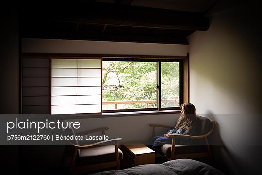 Mädchen sitzt am Fenster mit Rollo aus Reispapier - p756m2122760 von Bénédicte Lassalle