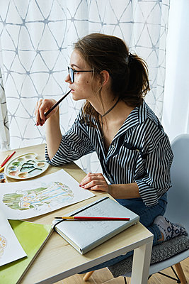 millennial girl draws fabulous images on paper while sitting at home - p1166m2171811 by Cavan Images