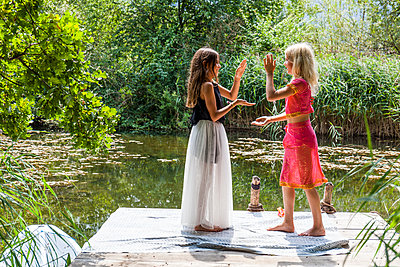Two girls standing on jetty at a pond in fancy dresses doing a hand clapping game - p300m2030491 von Tom Chance