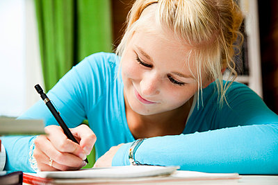 Girl writing in note pad - p4265749f by Tuomas Marttila